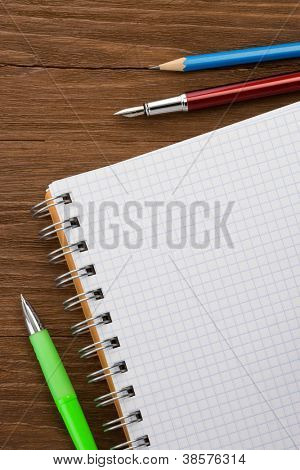 checked notepad and pen on wood background