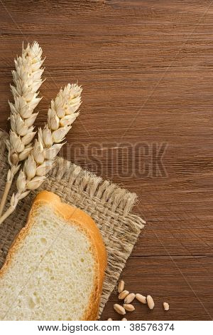 sliced bread and ears of wheat on burlap background