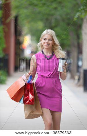 Glückliche junge Frau mit Einkaufstüten und Einweg Kaffee Becher auf Bürgersteig