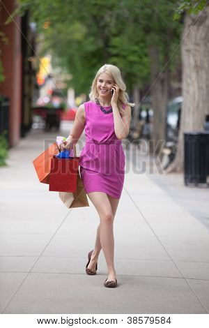 Portrait of a happy young woman with shopping bags using cellphone as she walks on sidewalk
