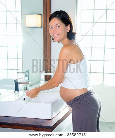 Beautiful pregnant woman on modern bathroom washing her hands