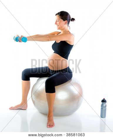 Beautiful pregnant woman at fitness gym with dumbells on aerobics ball