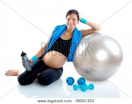 Beautiful pregnant woman at fitness gym relaxed with aerobics ball