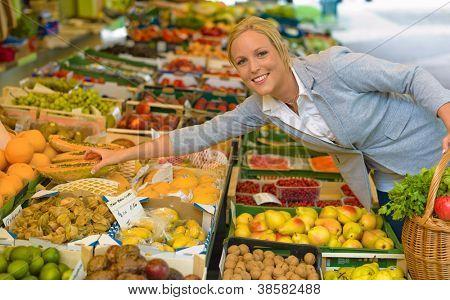 eine junge Frau kaufen Obst und Gemüse auf einem Markt. frisches und gesundes Essen.