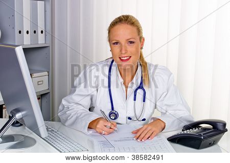a young female doctor with stethoscope in her doctor's office.
