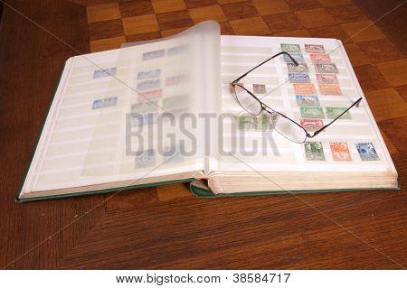 Par de óculos, sentado em um álbum de coleção de selos filatélicos