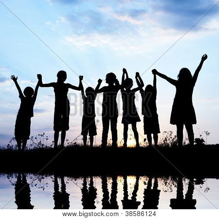 Happy children standing with outstretched arms on river