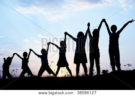 Children silhouettes holding hands up