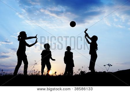 Happy children playing hand ball at sunset time
