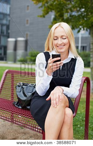 Smiling business woman sitting with smartphone on a park bench