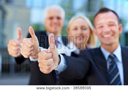 Happy successful business group holding their thumbs up