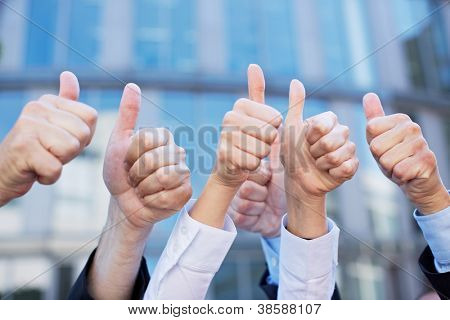 Many thumbs of different business people pointing up