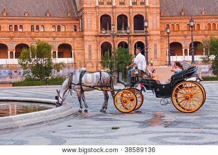 SEVILLA, SPAIN - JULY 19 : Tourists enjoy a trip on horsedrawn cart on Plaza de Espana, Seville on July 19 2008. Plaza de Espana was built in 1929.