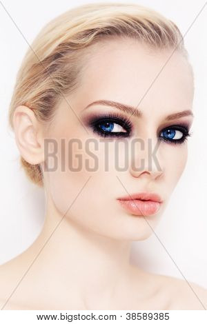 Close-up portrait of young beautiful woman with smoky eyes, on white wall