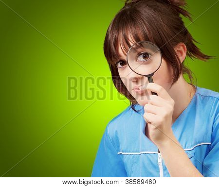 Woman looking through magnifying glass isolated on green background