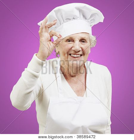 senior woman cook doing an excellent symbol against a pink background