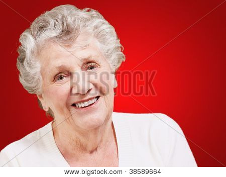 portrait of senior woman smiling over red background
