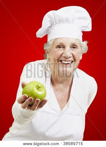senior woman cook offering a green apple against a red background