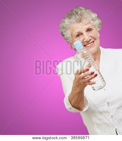 portrait of healthy senior woman holding a water bottle over purple background