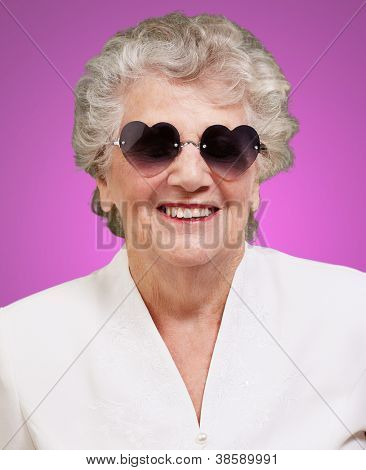 portrait of happy senior woman wearing heart glasses over pink