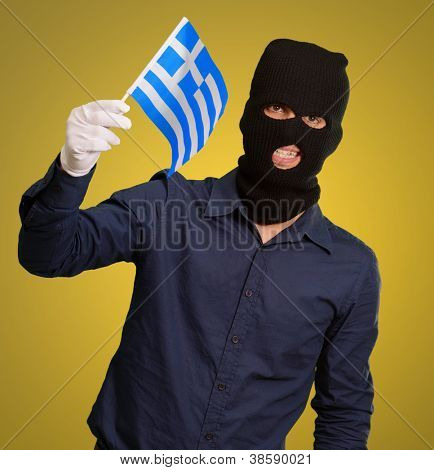Man wearing robber mask and holding flag on yellow background