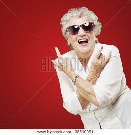 portrait of senior woman doing rock symbol over red background