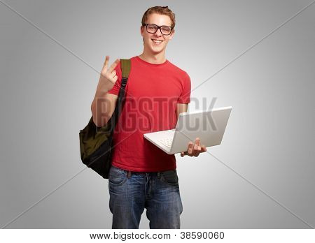 man holding laptop and backpack isolated on gray background