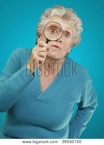 portrait of senior woman looking through a magnifying glass over blue background