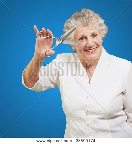 Senior woman holding scissors isolated on blue background