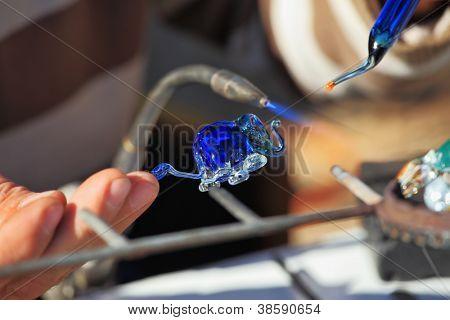 Heikle Arbeit der Glas-Gebläse. Das Künstler-Glas-Gebläse erzeugt eine anmutige kleine Figur von ein ele