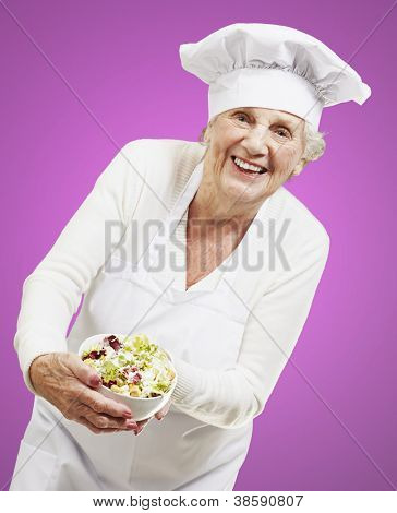 senior woman cook holding a bowl with salad against a pink background