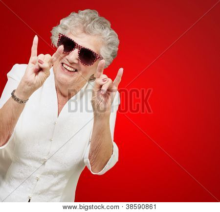 portrait of a happy senior woman doing rock symbol over red background