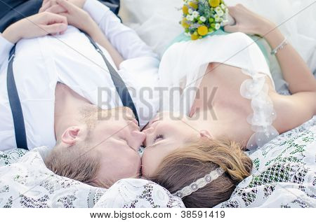 Lovely bride and groom holding hands while facing each other and smiling as the sun sets in the background