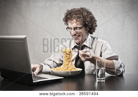 Businessman eating spaghetti with tomato sauce while using a laptop computer