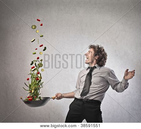 Businessman cooking vegetables with a pan