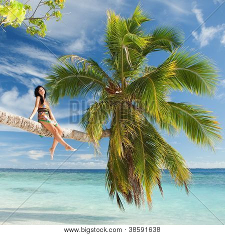 Fashion woman siting upon palm tree on the beach