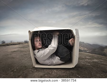 Man crouched into a box in a wasteland