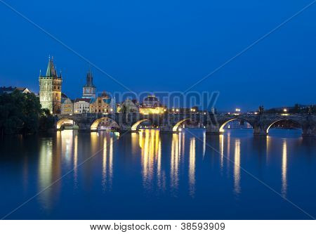 PRAGUE, CZECH REPUBLIC - AUG 5: Tourists crossing the Charles Bridge in early evening on August 5, 2012 in Prague, Czech Republic. Construction started in 1357 under the auspices of King Charles IV.