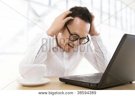 Depressed mid adult Asian business man scratching his head at office
