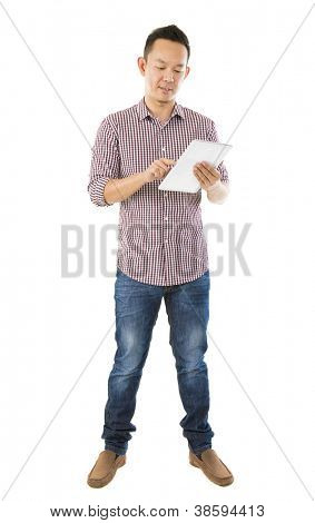 Fullbody Asian man using tablet computer standing over white background