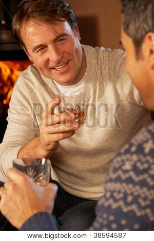 Two Middle Aged Men Relaxing While Sitting On Sofa and Drinking Whiskey