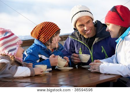 Family Enjoying Hot Drink In Cafe At Ski Resort