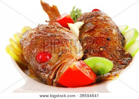 savory on plate: two fried fish served with tomatoes lemon and rosemary