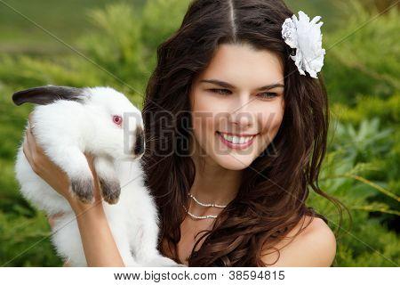 Novia joven sonriendo y sosteniendo conejo ute sobre Parque naturaleza de verano al aire libre, Alice in Wonderlan