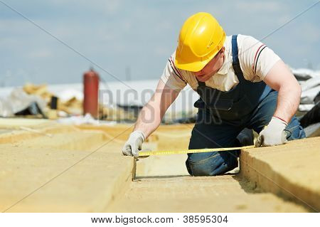 builder worker inspecting insulation material by measuring tape at roof