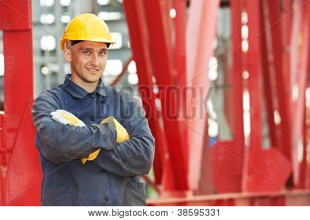 builder worker in uniform and safety protective equipment at construction site in front of metal construction frames