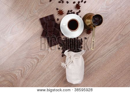 sweet hot drink : black coffee with beans in a white bag on a wooden table with stripes of dark chocolate and copper cezve