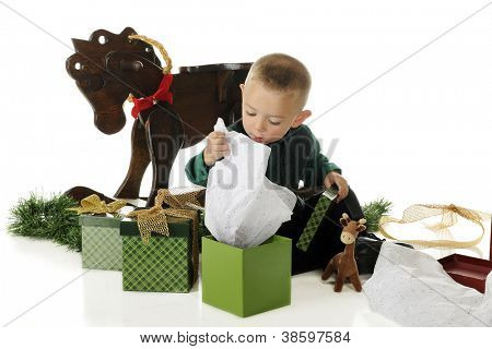 An adorable preschooler lifting the tissue paper, wondering what's inside his Christmas gift box.  On a white background.