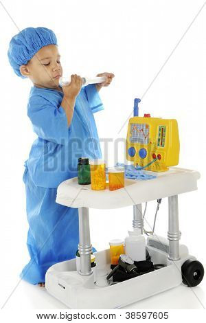 """An adorable preschool """"doctor"""" in blue scrubs checking the measurements on a large syringe as he stands by an emergency cart.  On a white background."""