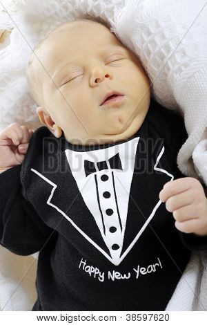 "Close-up of a sleeping newborn boy dressed in a black ""tux"" that welcomes the new year.  On a white background."